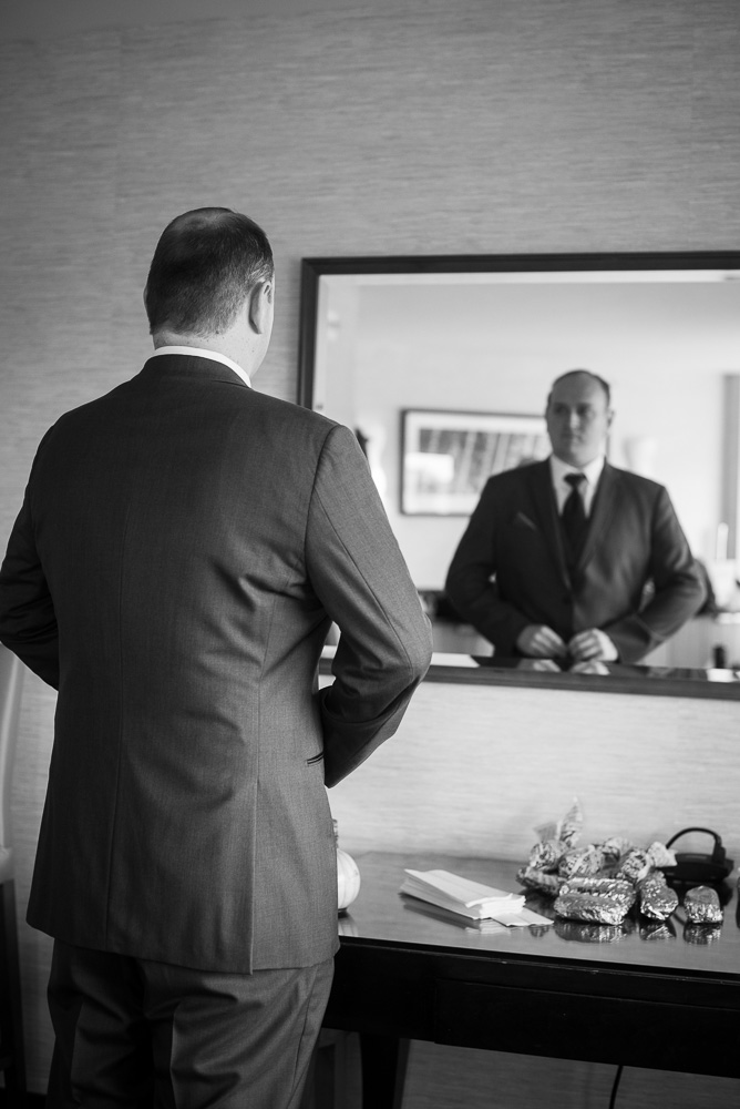 Groom buttoning his suit in front of the mirror in his Westin Washington Dulles Hotel room | Northern Virginia Documentary Wedding Photography