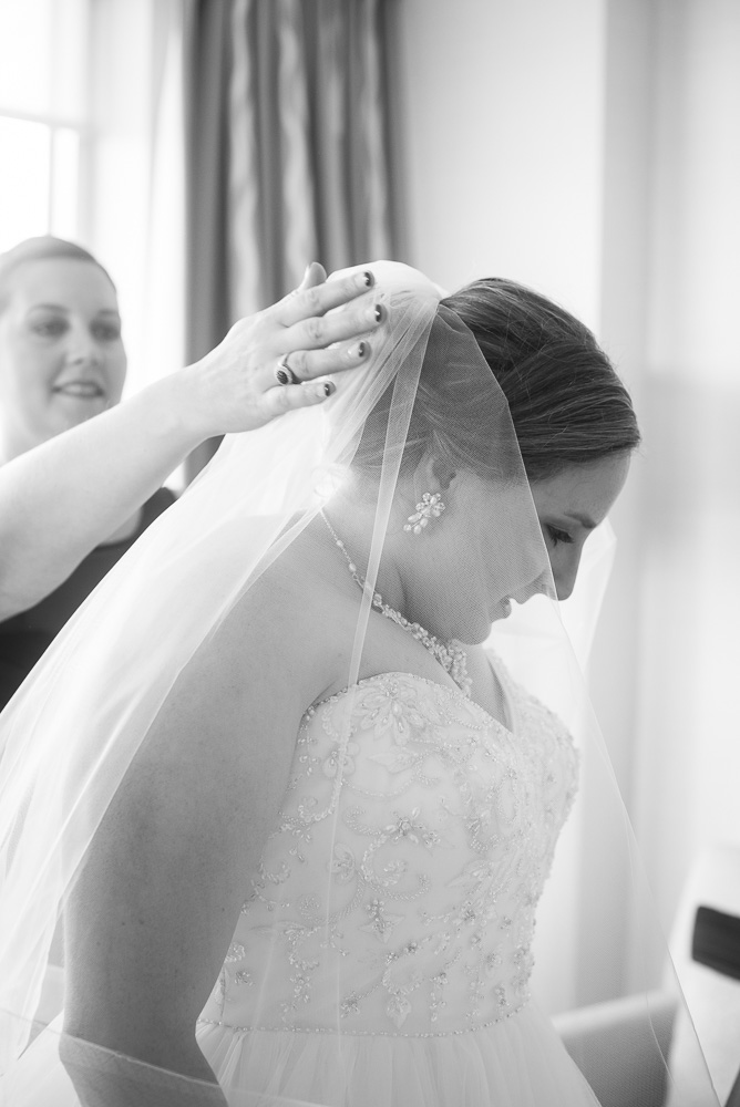 Bridesmaid helping the bride put on her veil | Documentary wedding photography in Herndon, Virginia