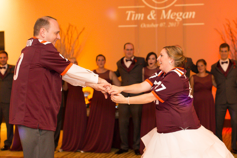 Bride and groom's first dance in their matching Virginia Tech jerseys | Maroon and orange uplighting by Dominion Wedding Entertainment