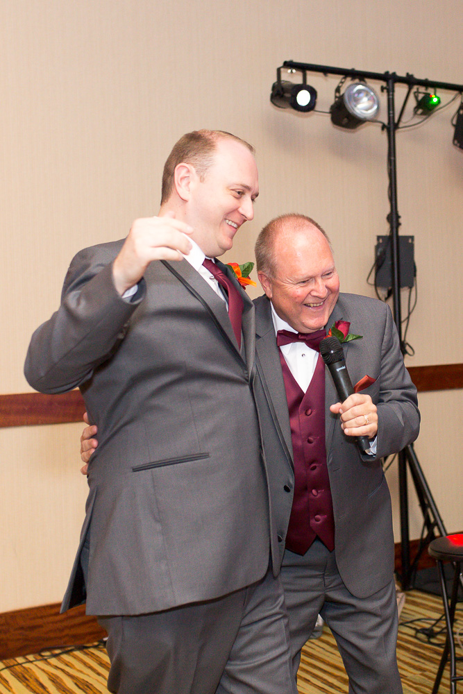 Fun candid moment between the groom and the father of the bride