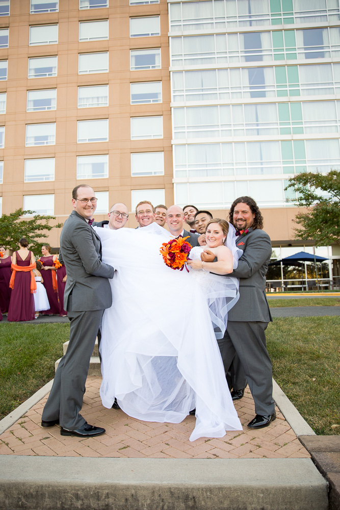 Groomsmen holding the bride in front of the Westin Washington Dulles Airport Hotel | Northern Virginia Wedding Photography