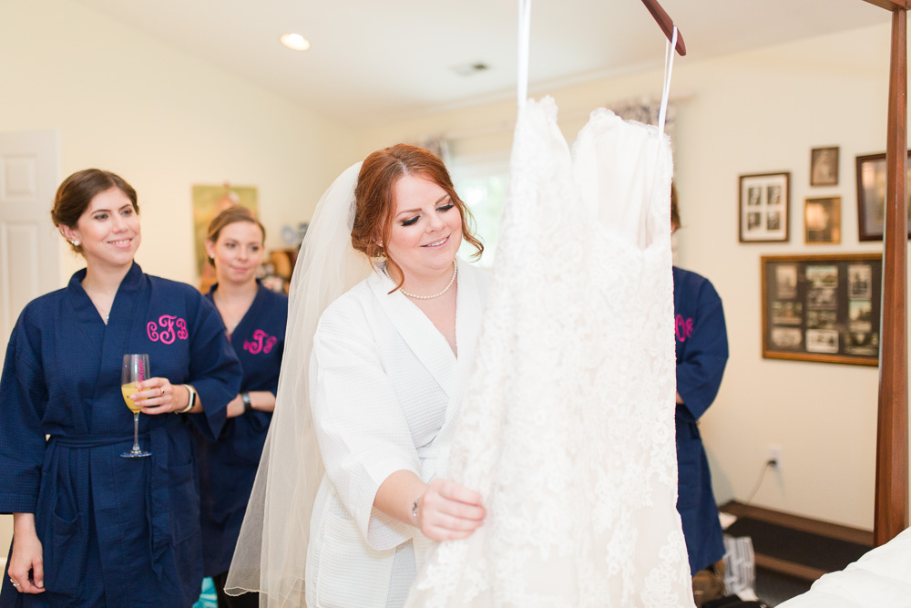 Bride and bridesmaids admiring the wedding dress from The Castle Prom and Bridal | Candid Richmond Virginia Wedding Photographer | Megan Rei Photography