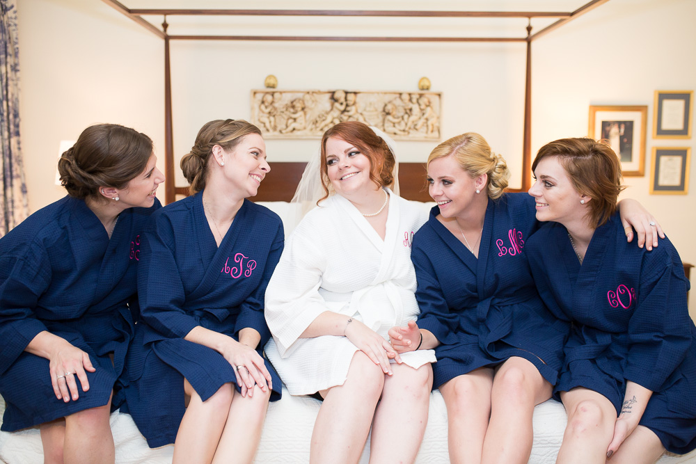Bride and bridesmaids sitting on a four poster bed in matching bathrobes while getting ready for the wedding | Fun Richmond Virginia Wedding Photographer | Megan Rei Photography