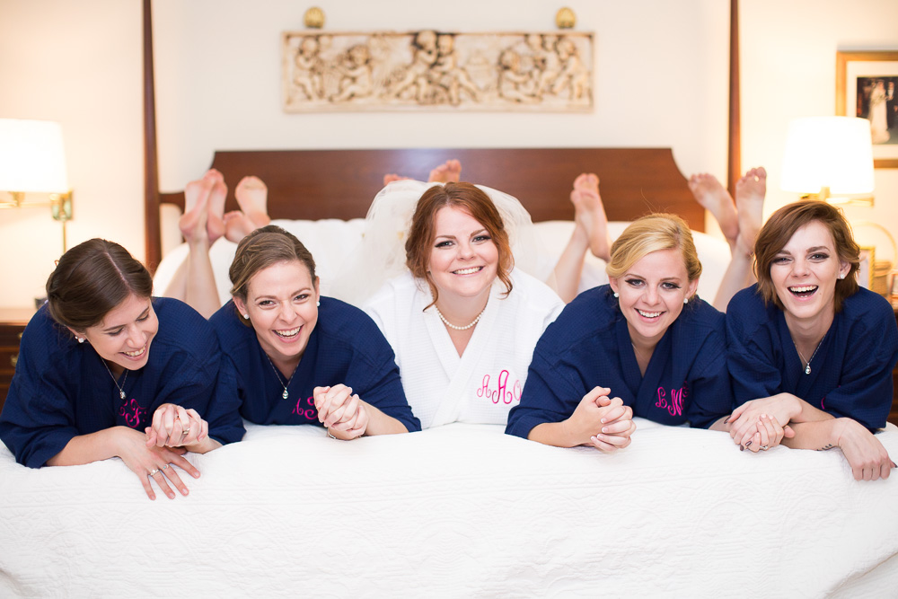 Fun photo of bridal party on the bed in matching bathrobes | Richmond Virginia Wedding