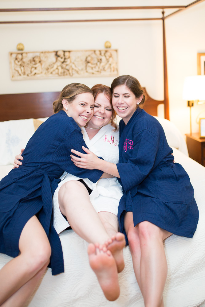 Candid picture of bride hugging her bridesmaids on the bed | Candid Richmond VA Wedding Photography