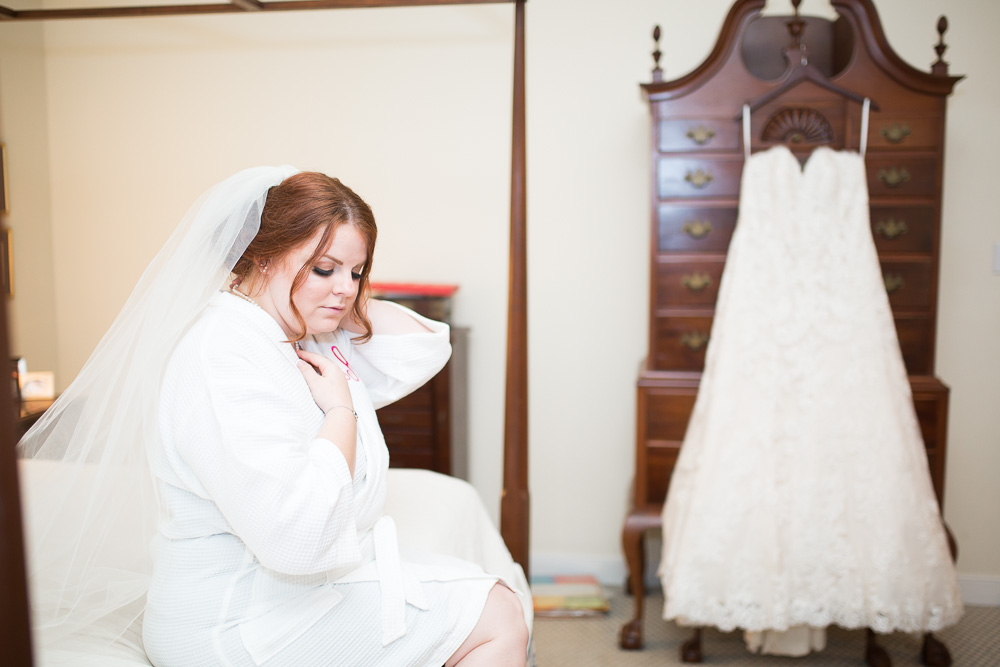 Bride sitting on the bed with wedding dress in the background | Wedding dress from The Castle Prom and Bridal | Richmond, Virginia Wedding