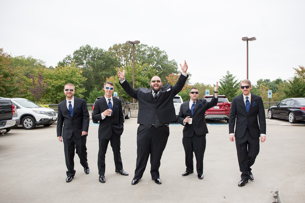 Groom and groomsmen having fun in the parking lot on their way to the wedding venue | Candid Richmond Wedding Photography