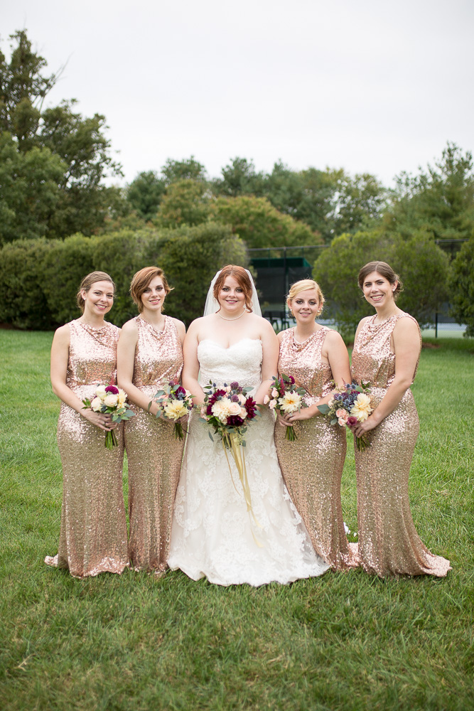Bride and bridesmaids in rose gold bridesmaid dresses