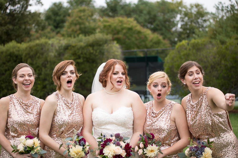 Candid photo of bride and bridesmaids, surprised when groomsman drops the rings
