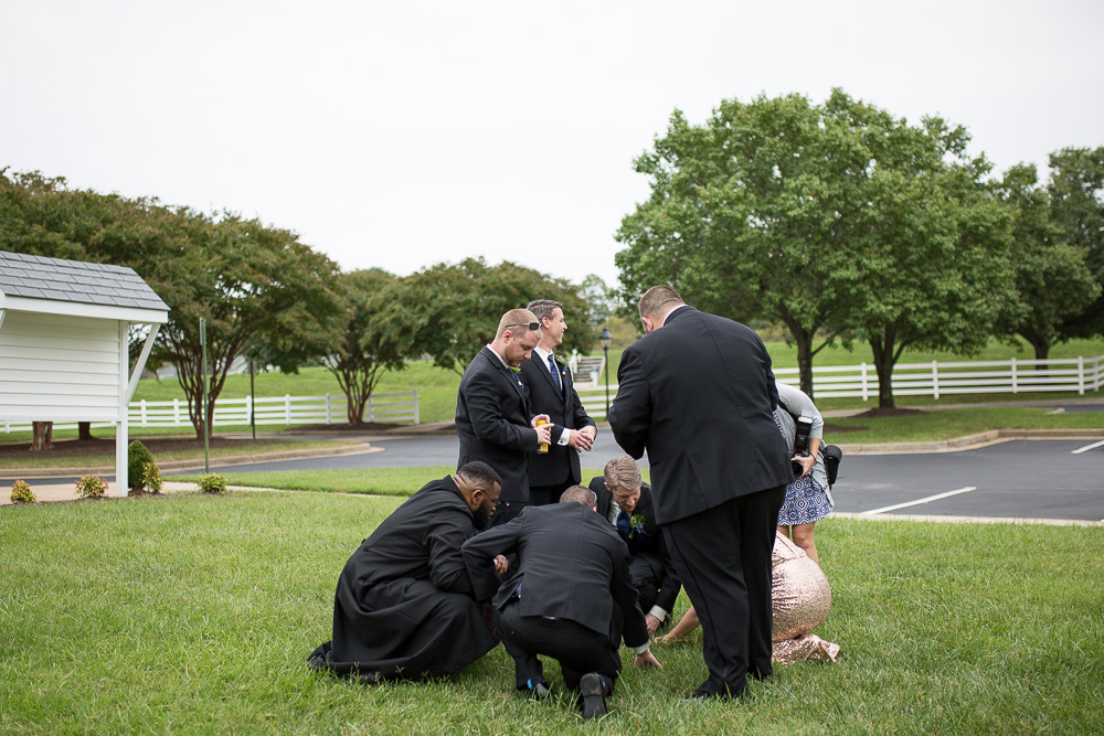 Groom and groomsmen looking through the grass for the wedding rings