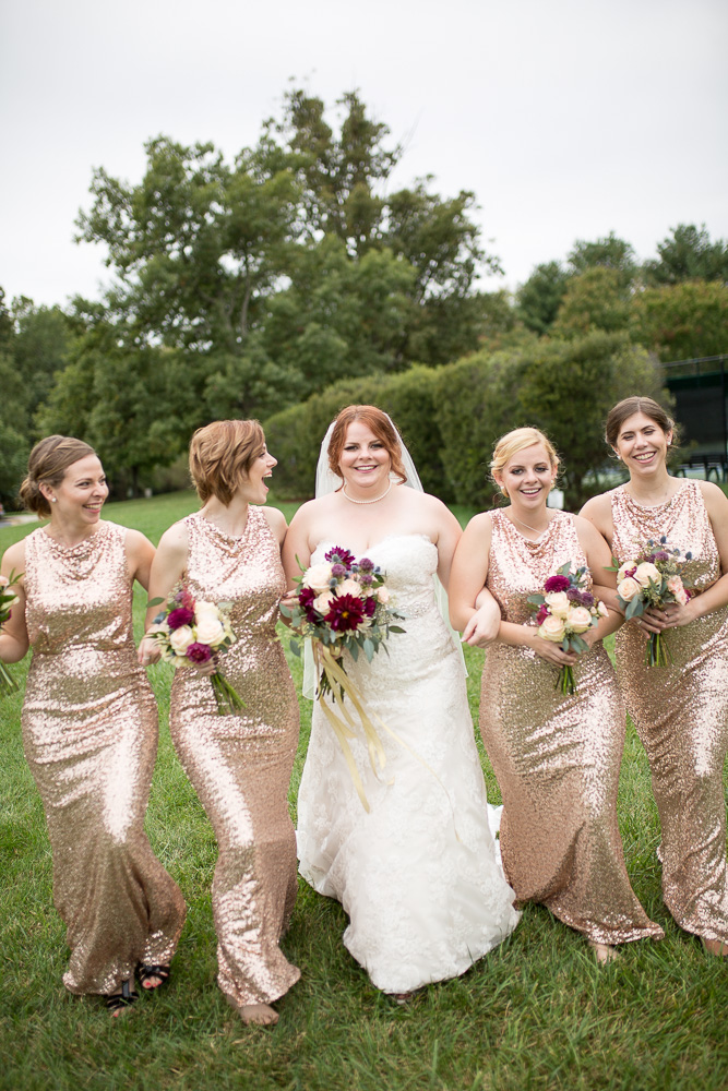 Candid picture of bridesmaids linking arms and walking at a Fox Hall Clubhouse wedding