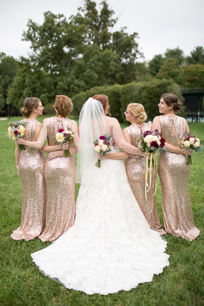 Back of wedding dress and rose gold bridesmaid dresses