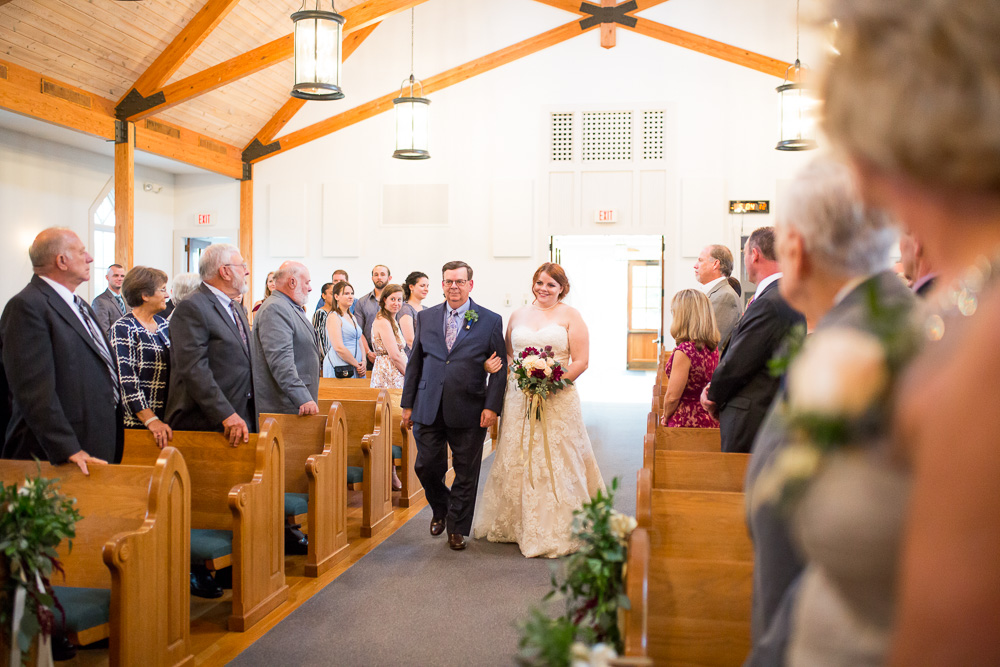 Bride walking down the aisle during wedding ceremony at Shady Grove United Methodist in Glen Allen