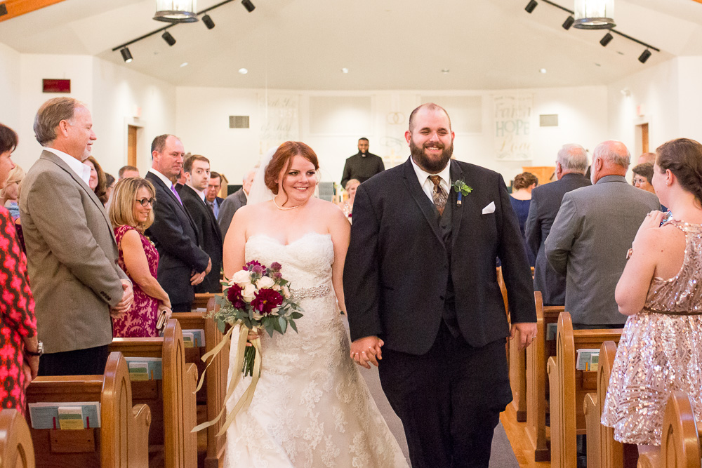 Smiling bride and groom during wedding processional at Shady Grove United Methodist - Short Pump