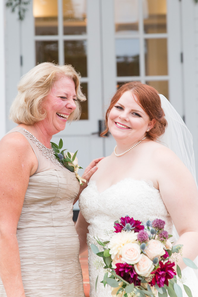 Candid wedding photo of bride and her mom laughing on the steps of Shady Grove Church in Glen Allen, VA