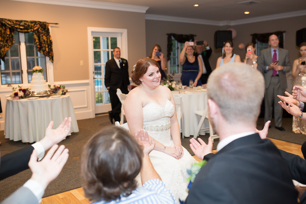 Bride smiling as she is serenaded during her wedding reception in Glen Allen