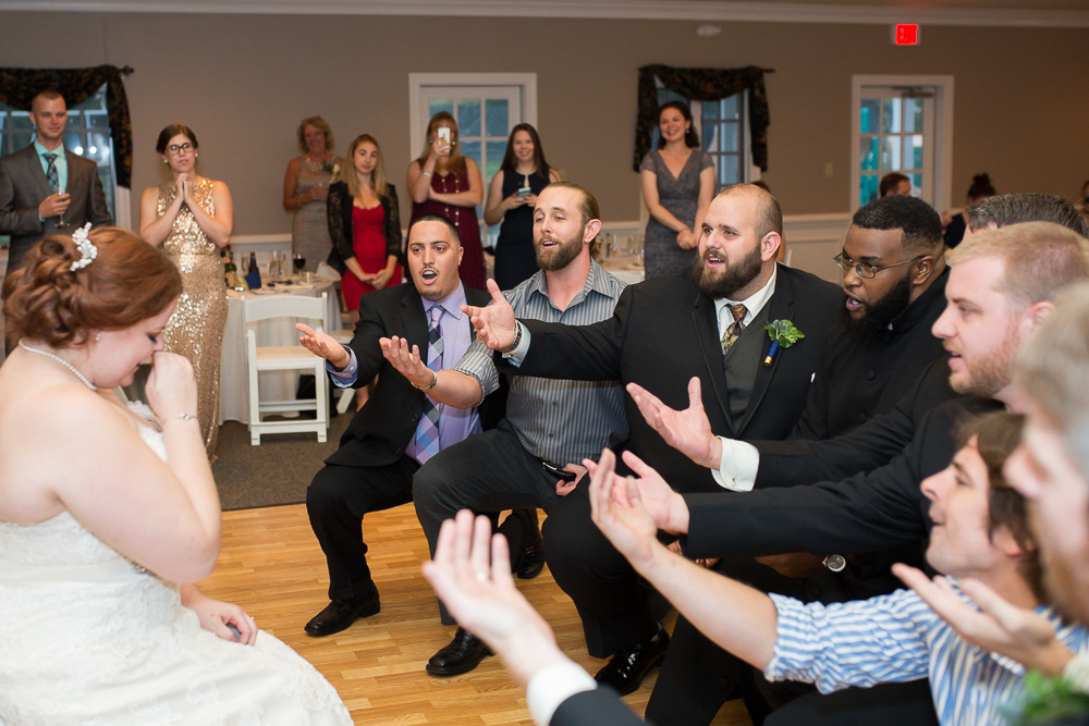 Groom and his a cappella group singing to the bride during wedding reception