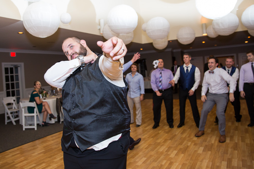 Groom throwing the garter during wedding reception