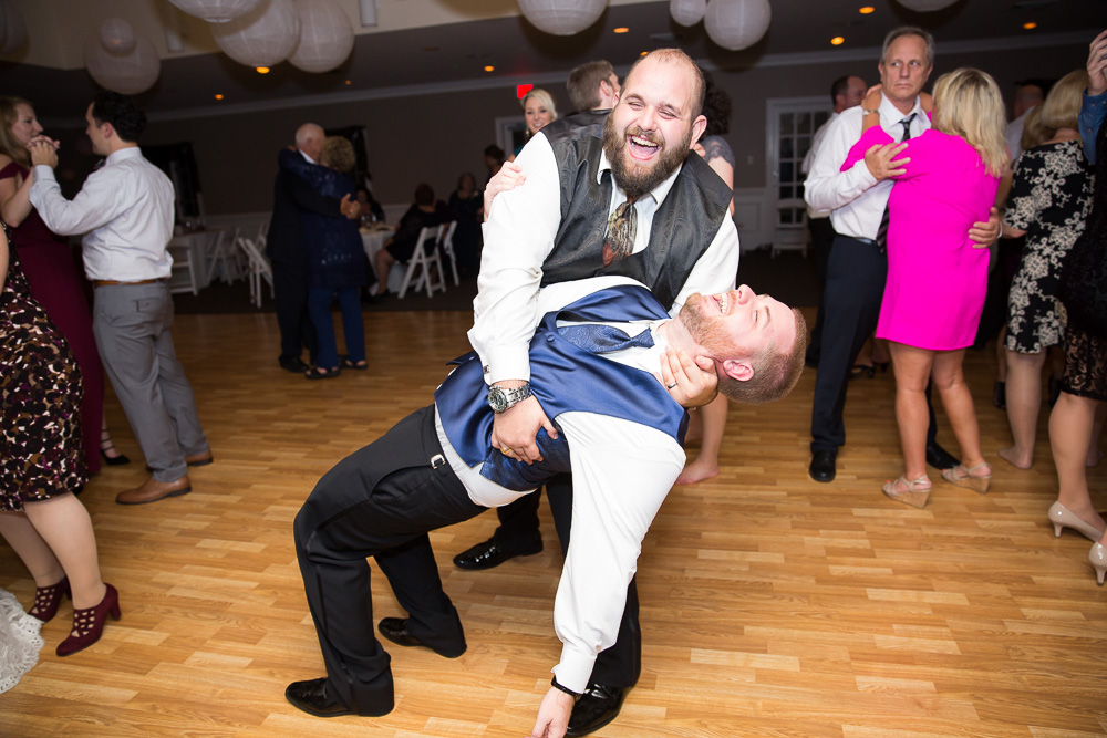 Groom goofing around on the dance floor with one of the groomsmen