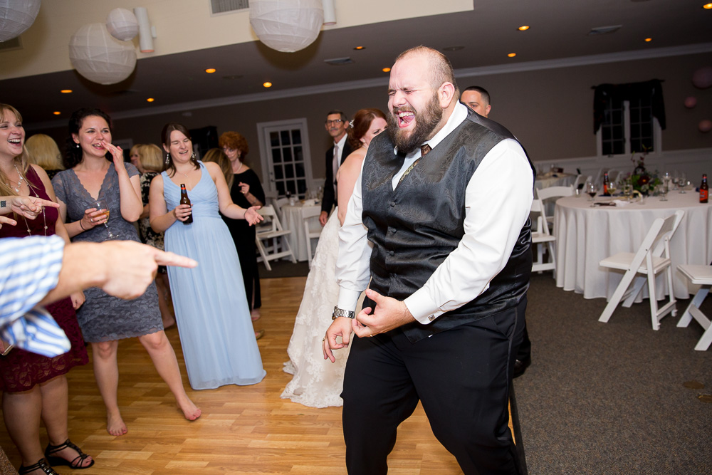 Funny photo of groom playing air guitar during his wedding at Fox Hall Clubhouse in Henrico, Virginia