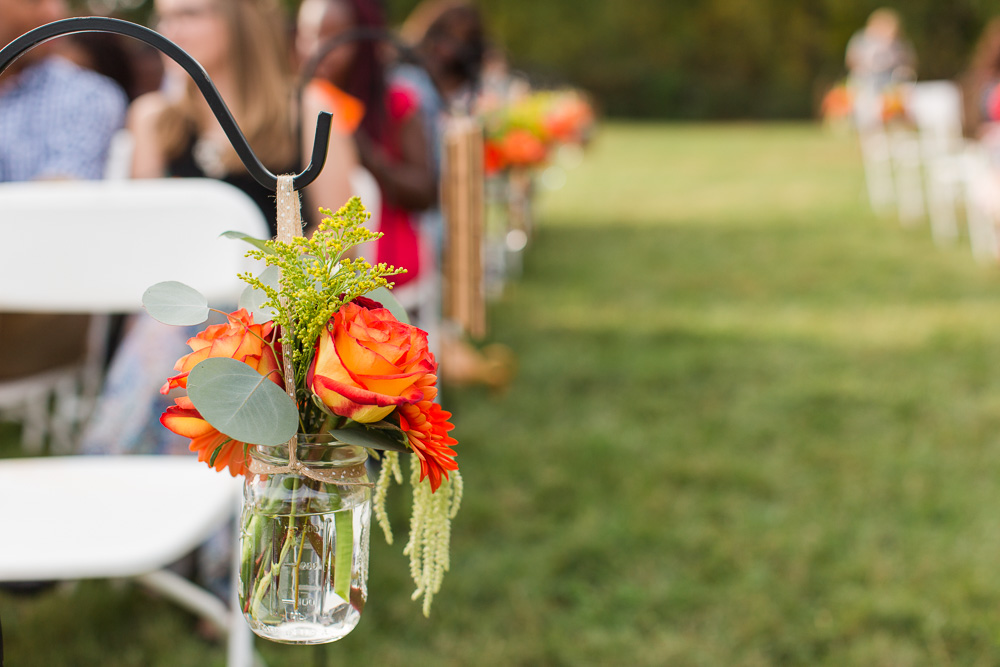 Orange flowers decorating the aisle at a Mountain Run Winery wedding | Melanie's Florist, Haymarket Virginia