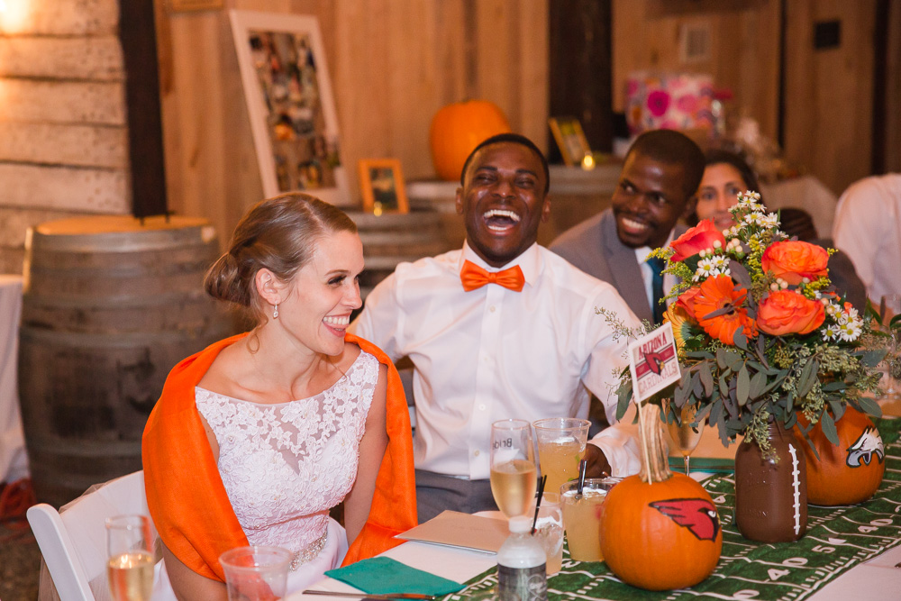 Candid laughter photo during the toasts inside the barn | Football-themed fall wedding at Mountain Run Winery