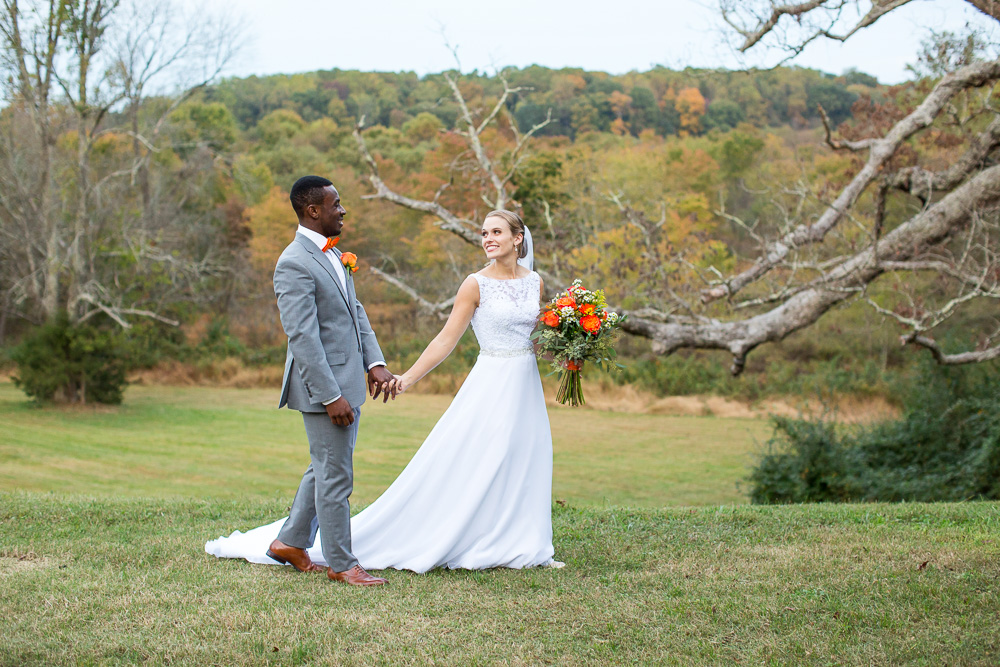Bride and groom walking through the field near the giant oak tree at Mountain Run Winery | Candid Culpeper Wedding Photographer | Megan Rei Photography