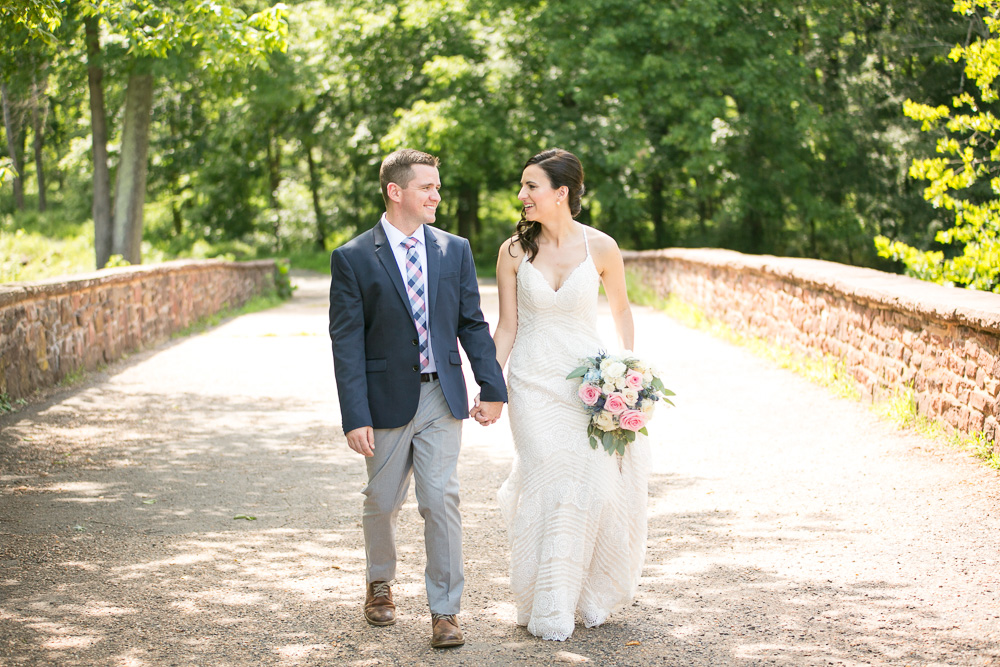Married couple holding hands as their walk across the Stone Bridge