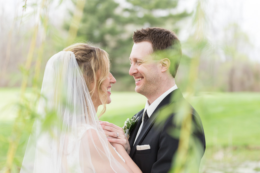 Wedding couple smiling during their portraits near a willow tree