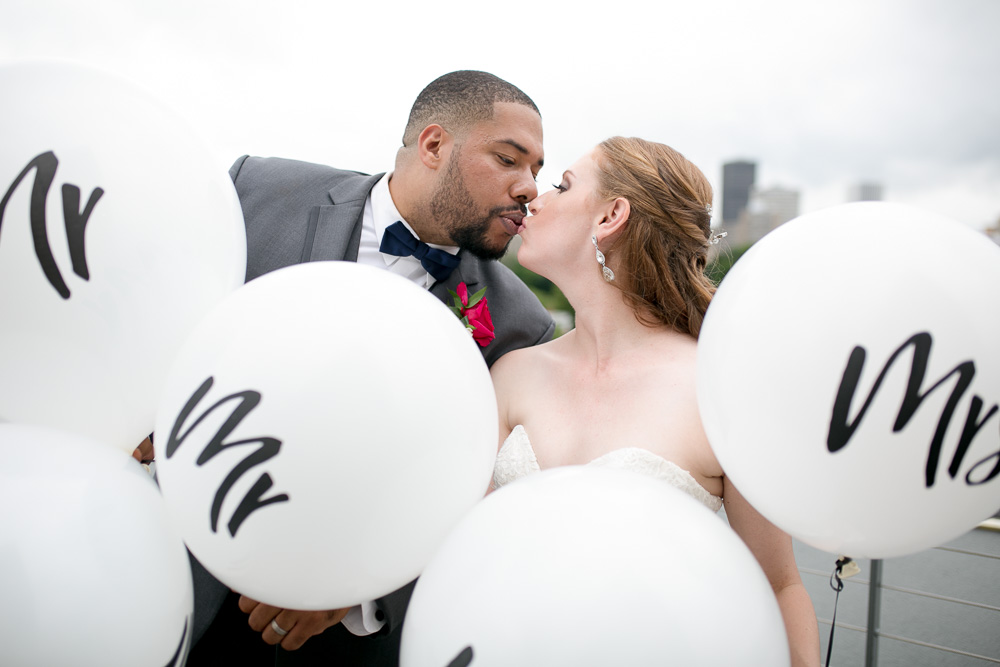 Wedding couple kisses while holding Mr. and Mrs. balloons at the Strathallan