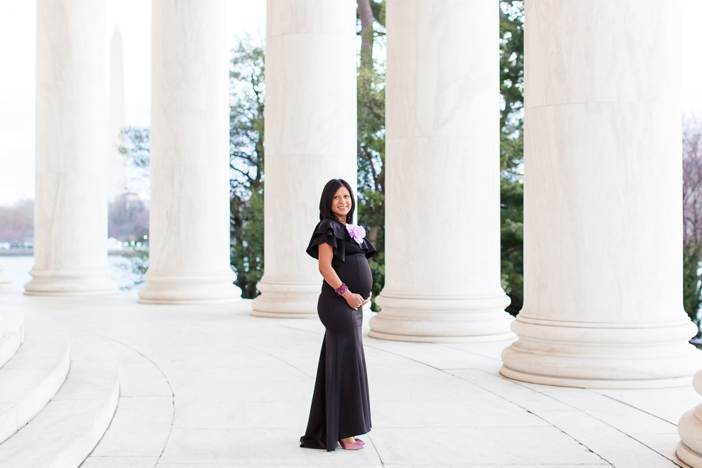 Mom-to-be posing in black maternity dress at the Jefferson Memorial with Washington Monument in the background