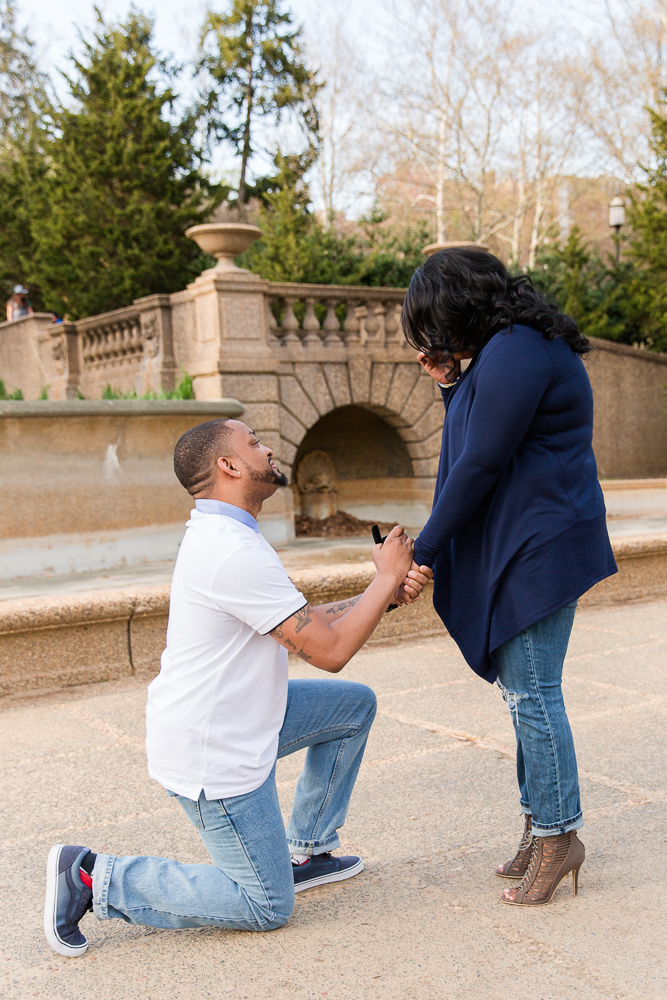 On one knee, showing her the ring | Wedding proposal at the Meridian Hill Park fountain | Candid DC Engagement Photographer