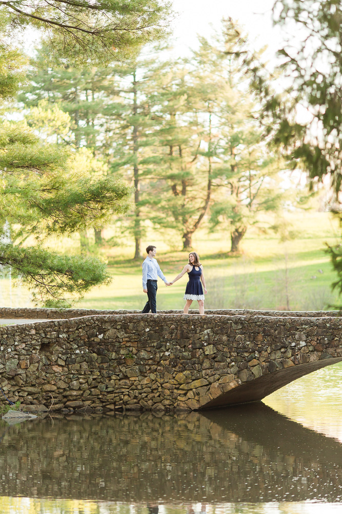 Engagement picture walking across the stone bridge over the lake in Warrenton, Virginia | Megan Rei Photography