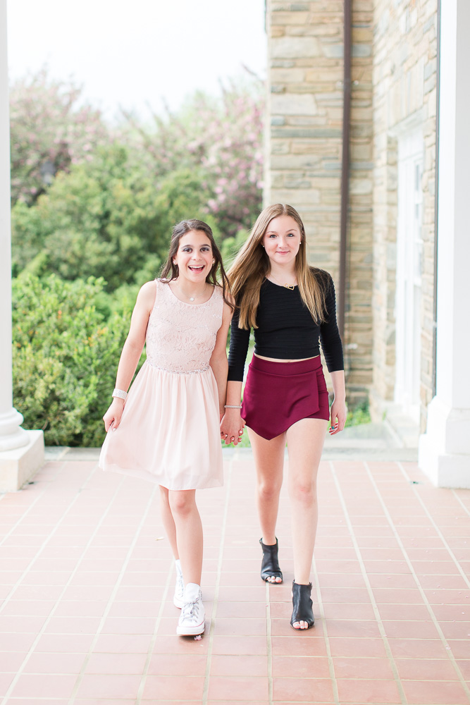 Friends holding hands on the covered front porch of the Glenview Mansion | Rockville, MD Bat Mitzvah Photography