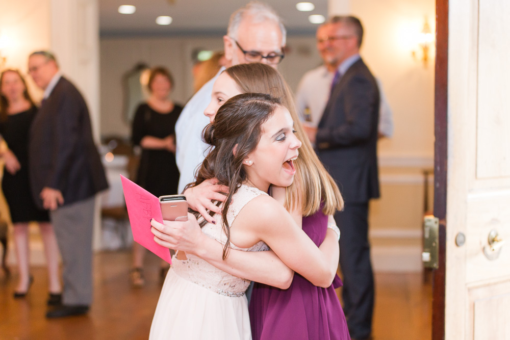 A happy hug when one of her friends arrives | Glenview Mansion Bat Mitzvah