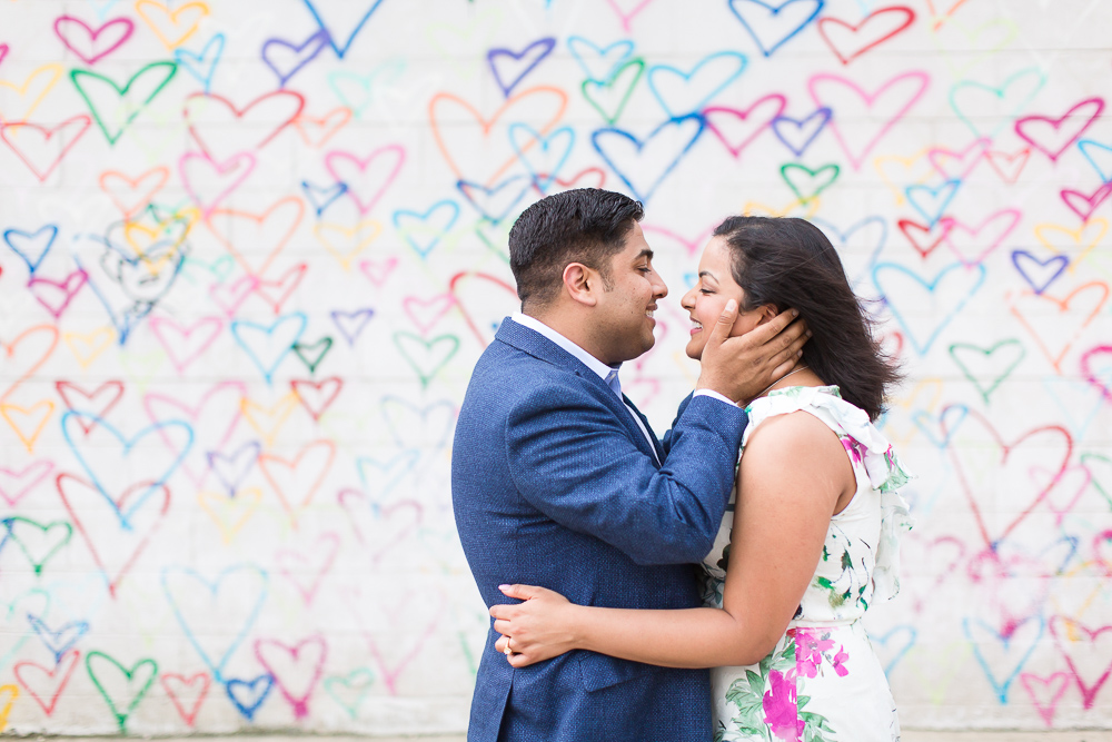 Sweet engagement picture by the heart wall at Union Market | Washington DC Candid Engagement Photographer | Megan Rei Photography