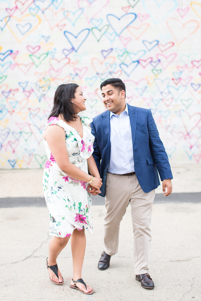 Engaged couple in front of the heart wall mural at Union Market