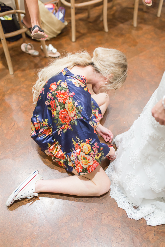 Bridesmaid cutting off loose strings from the wedding dress | Candid Crozet Wedding Photography