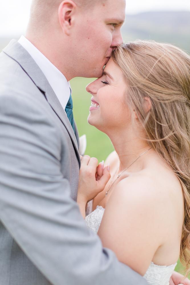 Groom giving bride a kiss on the forehead | King Family Vineyards Wedding Photos | Crozet Virginia Photographer | Megan Rei Photography