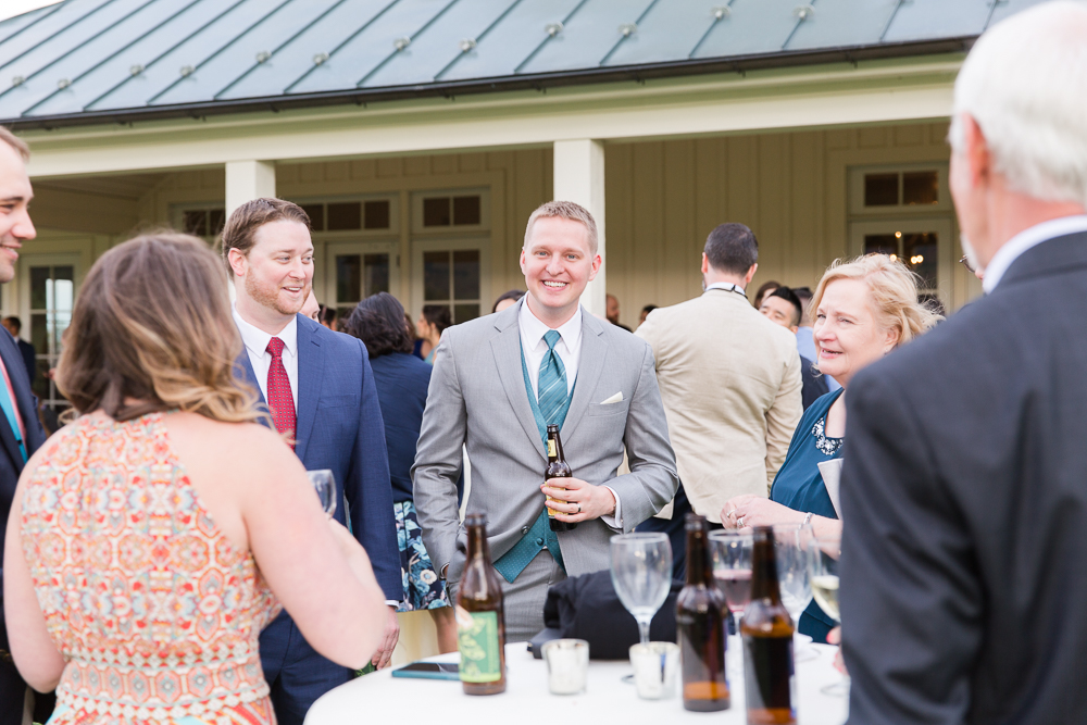 Candid picture of the groom with wedding guests during cocktail hour