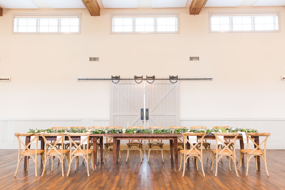 Beautiful wooden farm table with greenery as the head table for wedding reception at King Family Vineyards | Best Winery Wedding Venues in Virginia