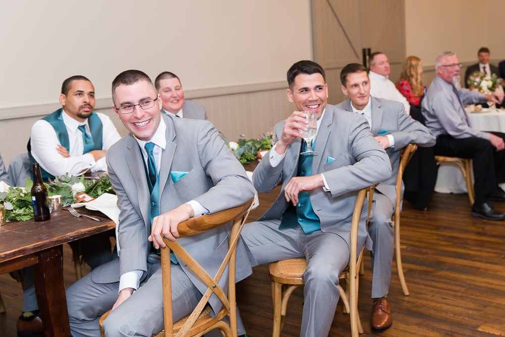 Candid photo of groomsmen laughing during the wedding toasts