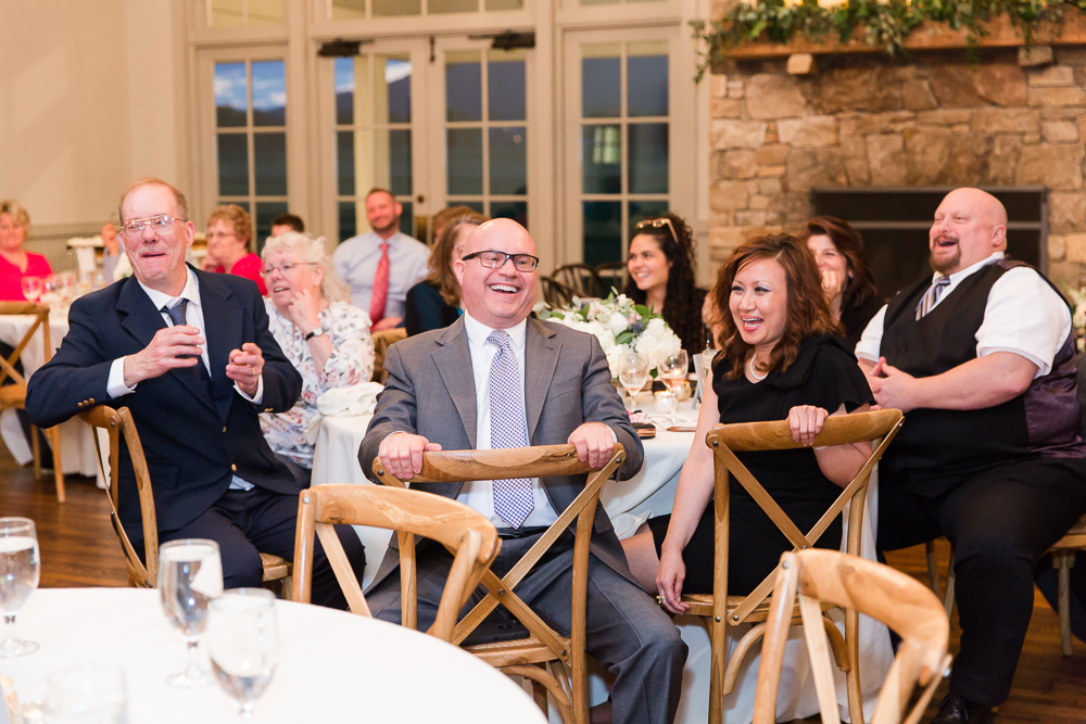 Candid picture of wedding guests laughing during the reception at King Family Vineyards | Candid Wedding Photography in Crozet