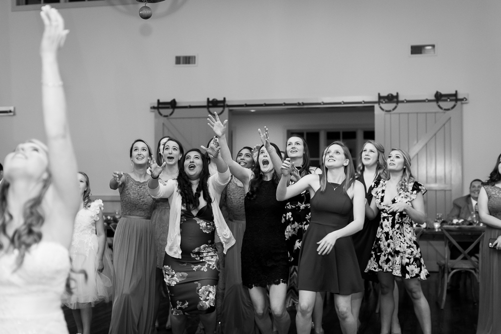 Single wedding guests reaching for the bouquet | Candid Crozet Wedding Photographer