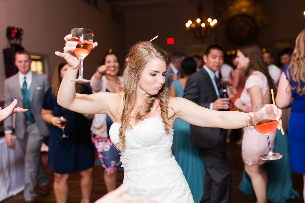 Bride dancing with two wine glasses during her wedding reception at King Family Vineyards | Fun and candid wedding photographer in Crozet, Virginia
