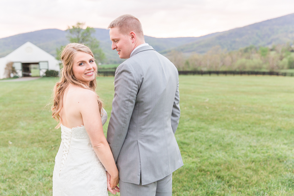 Sweet wedding photo with bride looking back at the camera | Sunset at King Family Vineyards