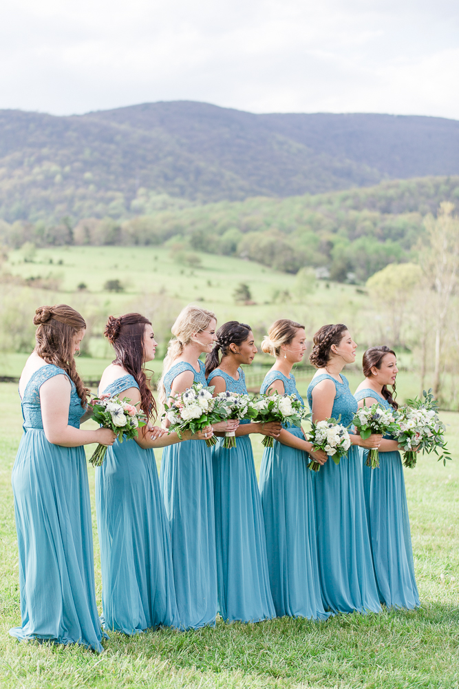 Bridesmaids in teal dresses standing during the wedding ceremony