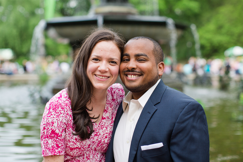 Smiling engaged couple in front of the Bethesda Fountain in New York City