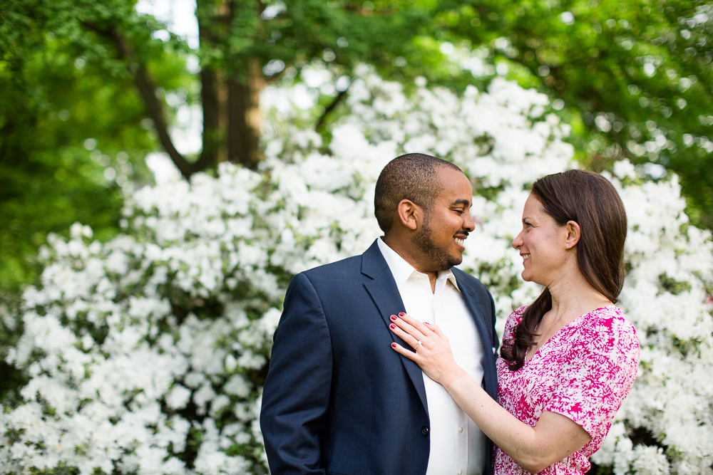 Happy engaged couple in front of white flowering bush in Central Park | Best engagement photos in NYC