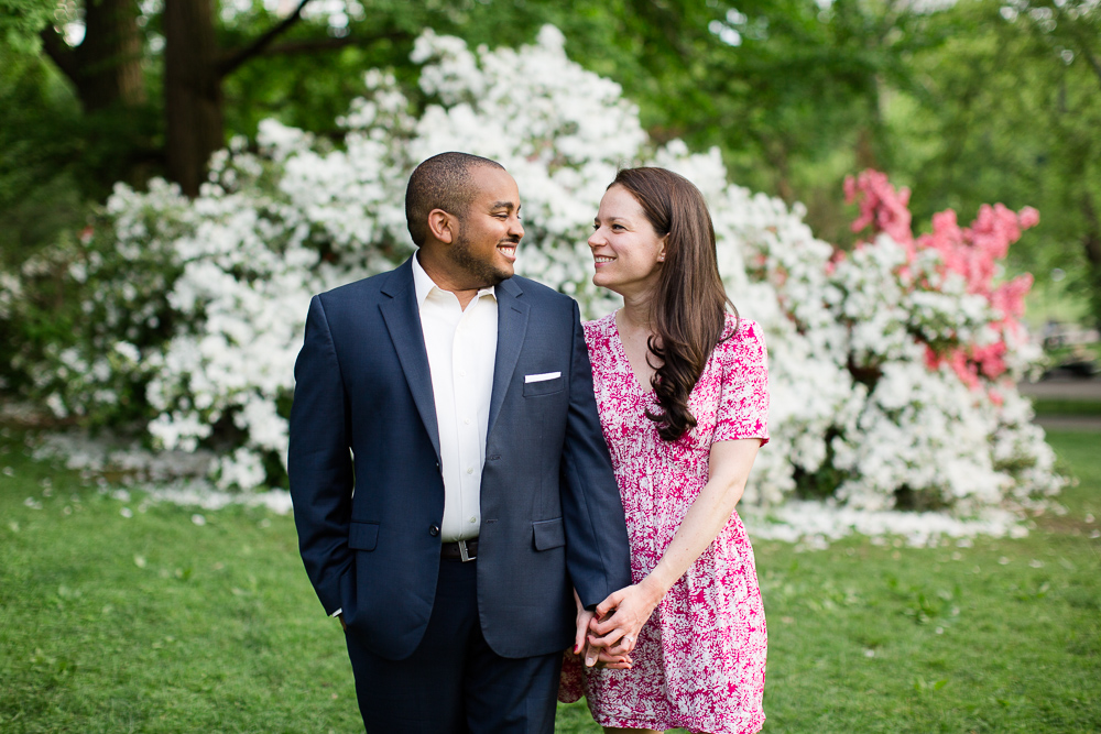 Happy engaged couple in front of white flowering bush in Central Park | Candid engagement photos in NYC